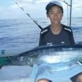 トローリングで釣れたオキサワラを抱えた少年