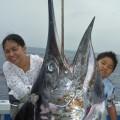 女性が180kgのカジキを釣り上げ子供と記念撮影2015年6月26日クレーンズ沖縄、鶴丸のトローリングにて船長は鶴巻守