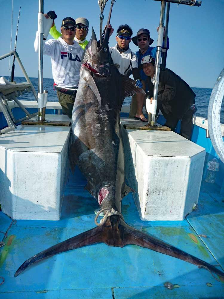 真中にカジキが頭を上にして吊るされ左に二人、右に三人のアングラー(釣人)