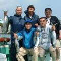 釣れた魚で記念撮影している5人の男