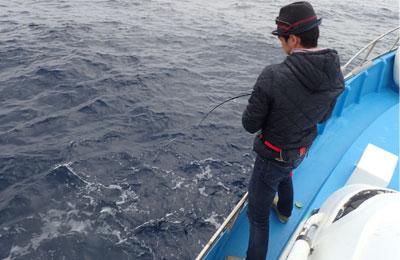 魚を釣っている帽子の男