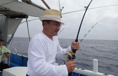 トローリングでカツオを釣っている帽子の男性