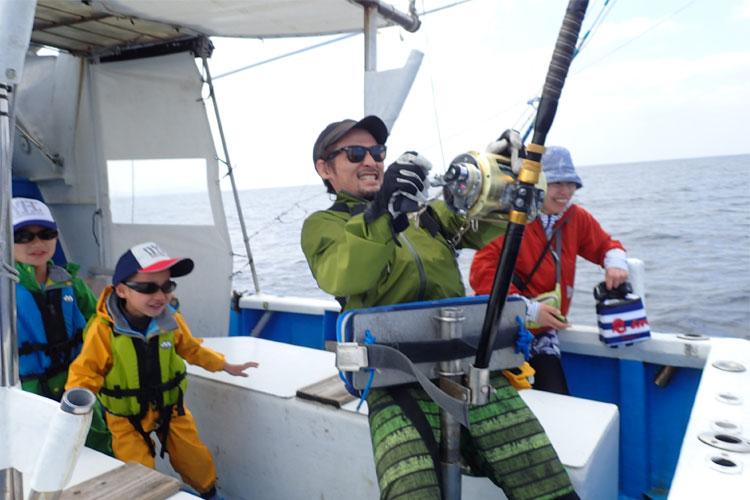 沖縄のトローリングでサメとファイトしているお父さんと後ろで見守る家族