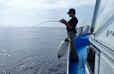 沖縄のジギングでカンパチを釣っている男性