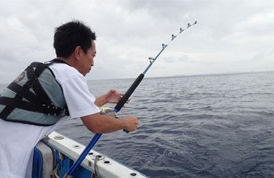 沖縄のトローリングで魚と格闘している男性