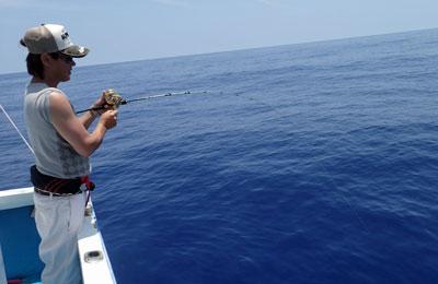 沖縄のジギングでカンパチ釣りでファイト中の男性