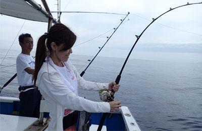 トローリングでダイバンカツオを釣り上げている女性