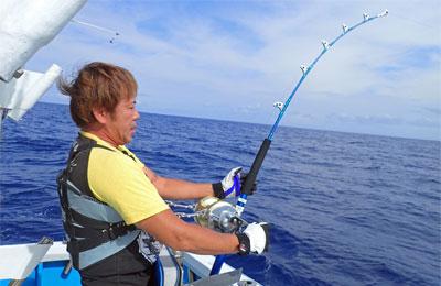 クレーンズ沖縄のトローリングで30lbロッドにてカジキとファイトしている男性