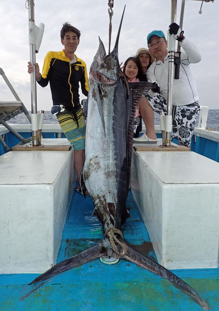 釣り上げた90kgのカジキと関西から沖縄へ釣りに来たメンバー4人