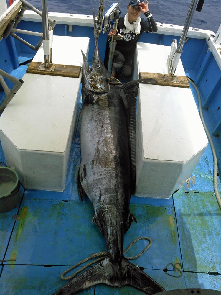 船のデッキに引き上げた150kgの巨大カジキとアングラーの女性