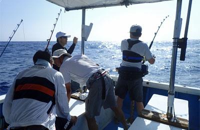 トローリングにてカジキが掛かった船上に4人の男性