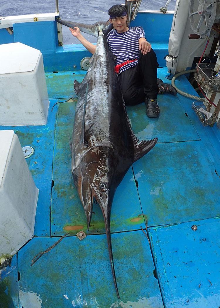 トローリングで釣れたカジキと尾を右手で抱えている男性