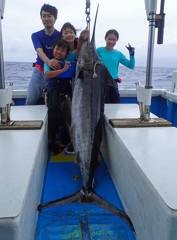 沖縄のトローリングでカジキを釣り上げた4人のファミリーとブルーマーリン