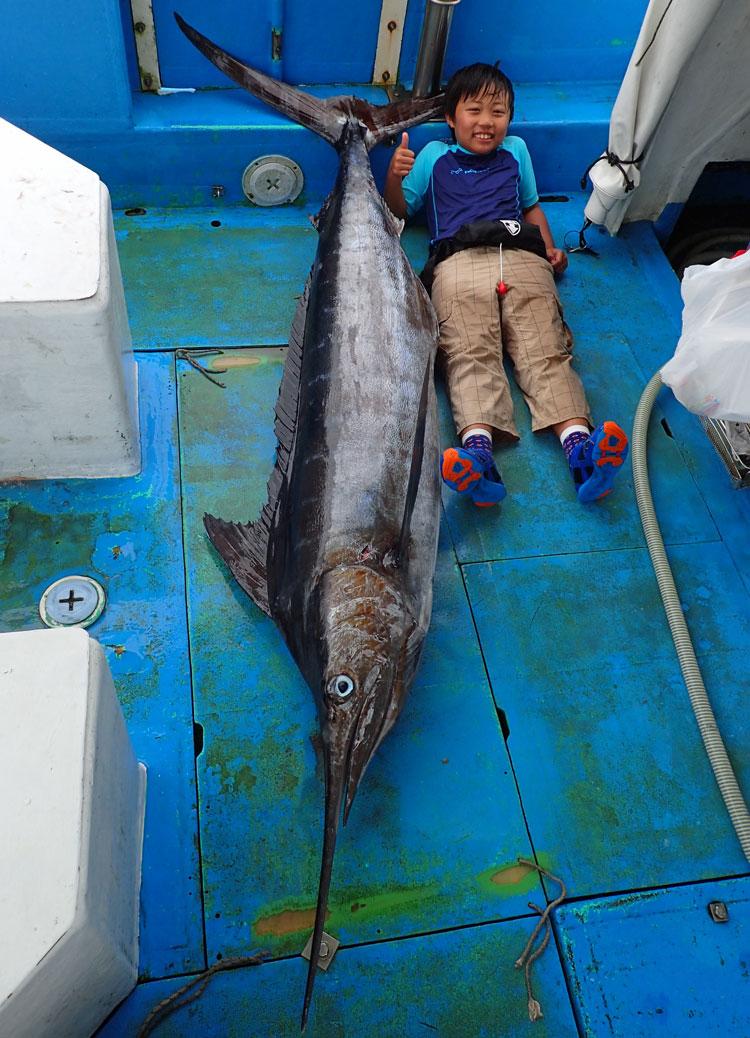 釣り上げたカジキの横に仰向けで記念撮影している少年