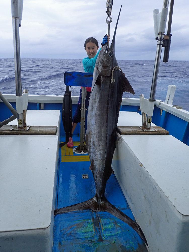 釣り上げたカジキと記念撮影している少女
