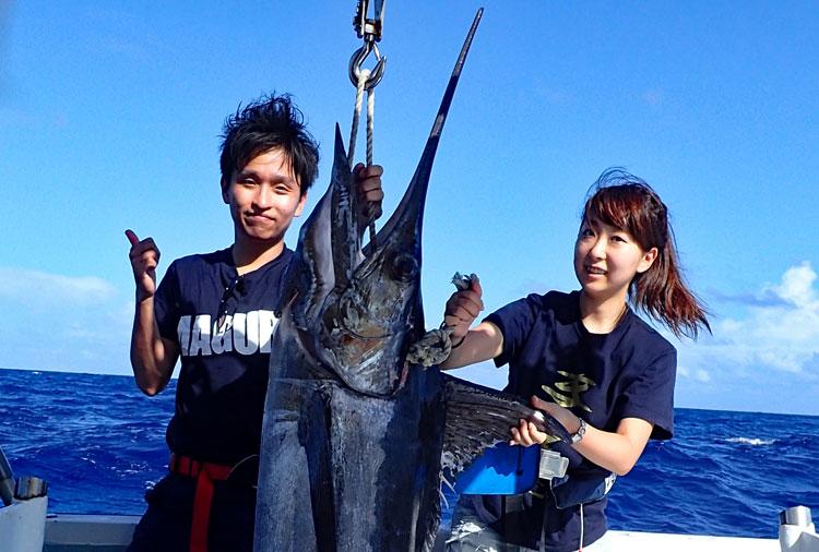 真中に釣り上げたカジキと左に男性、右に女性