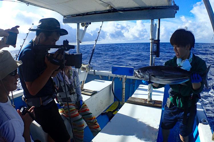 本カツオを釣った女性と撮影しているカメラマン