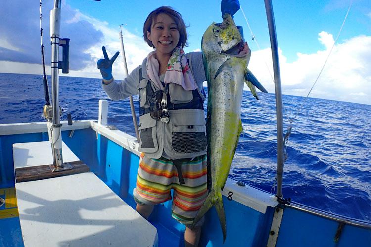 トローリングでシイラを釣ったピースサインの女性