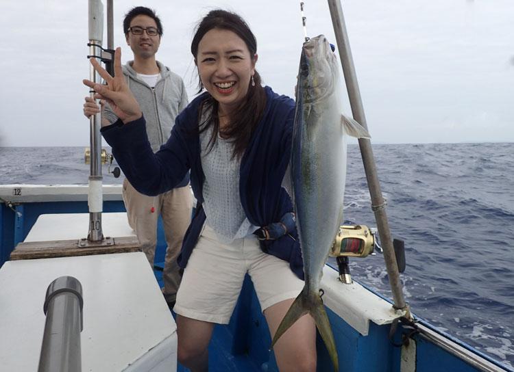 ツムブリを釣ったピースサインの女性