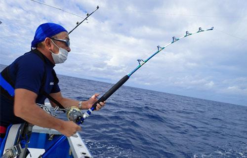 沖縄のトローリングでマグロを釣っている男性