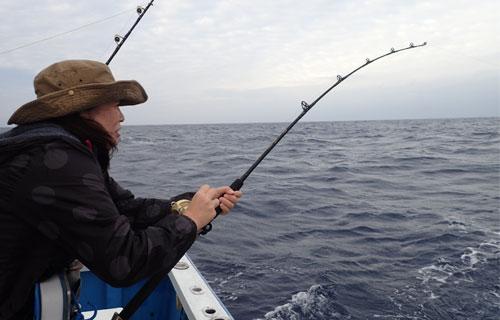 トローリングで魚を釣っている帽子の女性