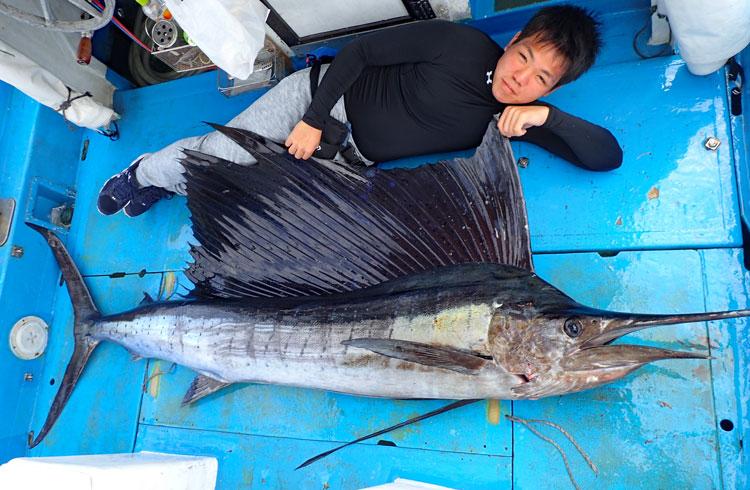 ジギングで釣り上げた50kgのバショウカジキとアングラーの高校生