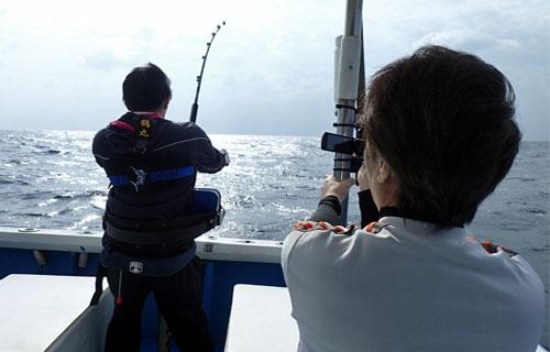 カジキを釣っている大学生とビデオ撮影している父