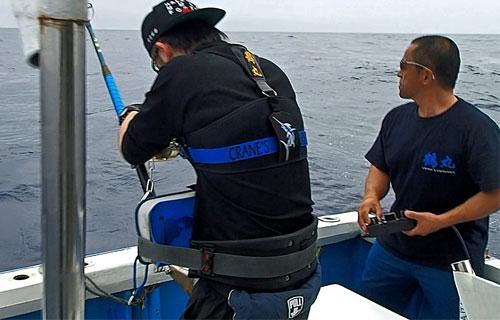 カジキとファイトしている男性と船長