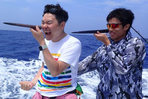 自分で釣り上げたカジキのツノを持っている二人の男