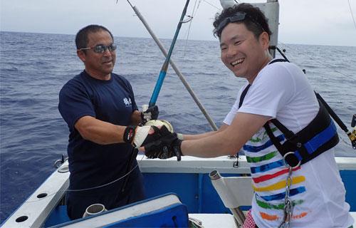 カジキを釣って握手している鶴丸船長とアングラー
