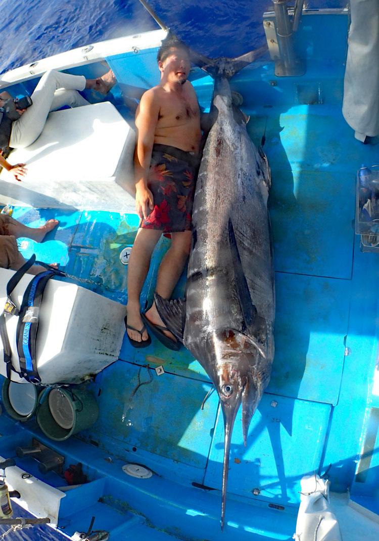 釣り上げた150kgのカジキと横に185ccmの男性