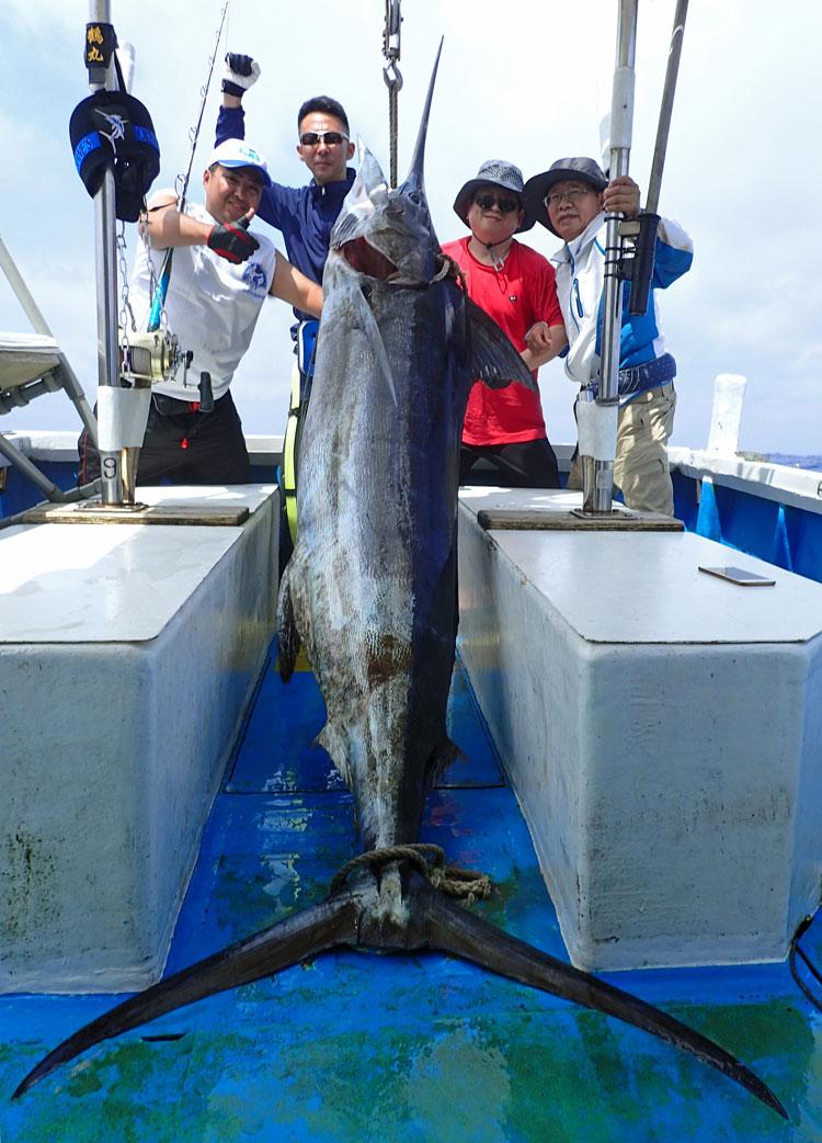 釣り上げた100kgのカジキと記念撮影している中国人の4人