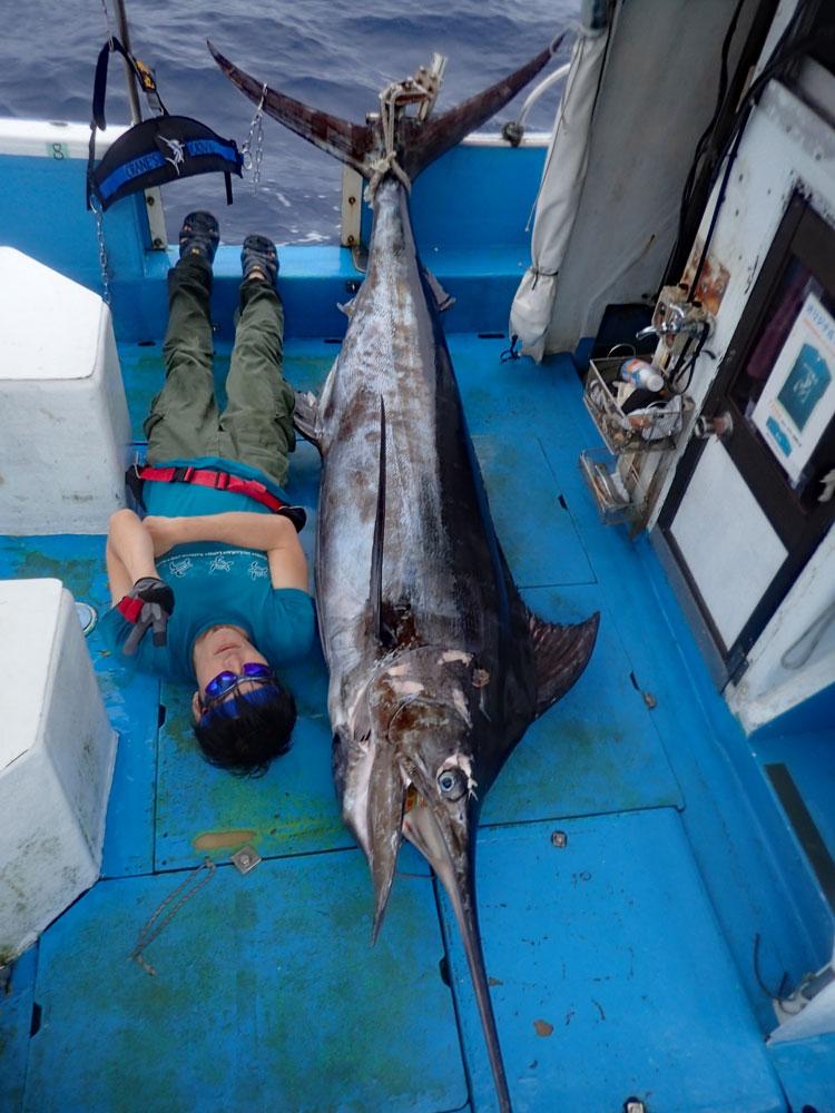 150kgのカジキとあおむけに寝ているアングラー
