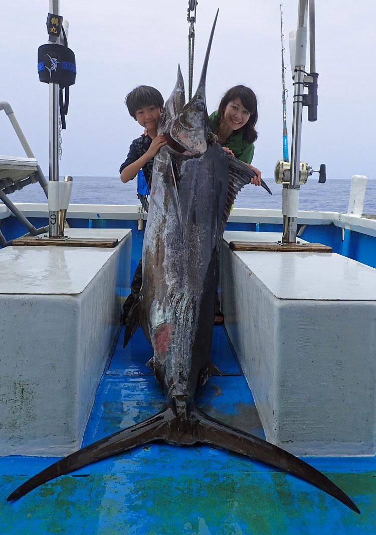 頭を上にぶら下げた100kgのカジキと釣った10才の少年と母