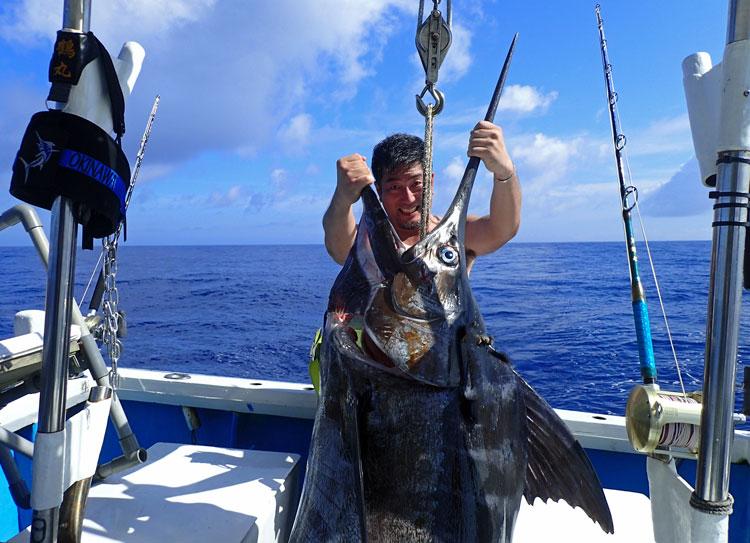釣り上げた150kgのカジキの口の間から顔をのぞかせる男