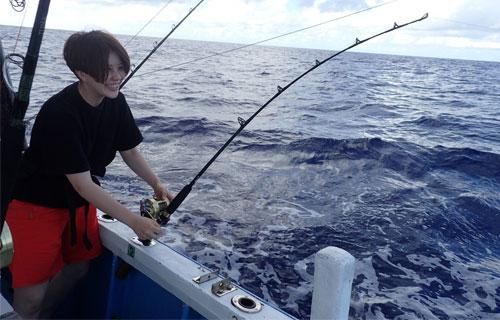 小マグロを釣っている若い女性
