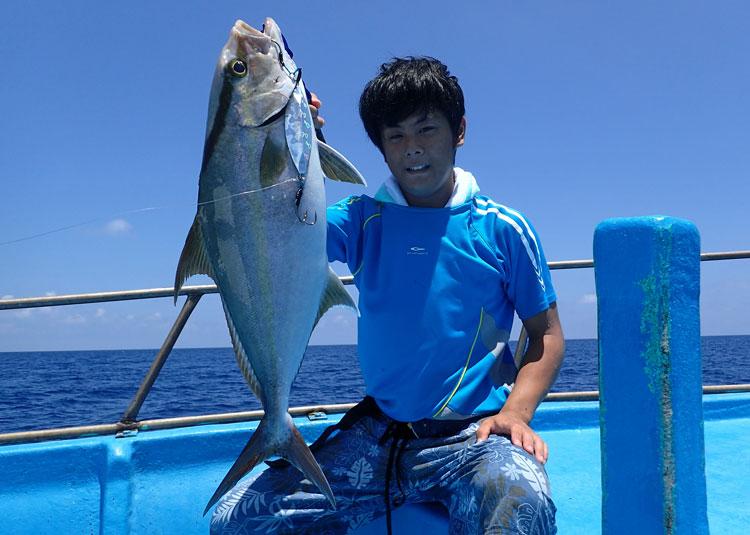 ジギングで釣ったカンパチと青いシャツの男性