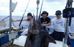 釣り上げたカジキと三人の若い男
