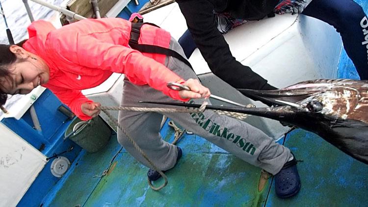 バショウカジキを船に引き上げる女性