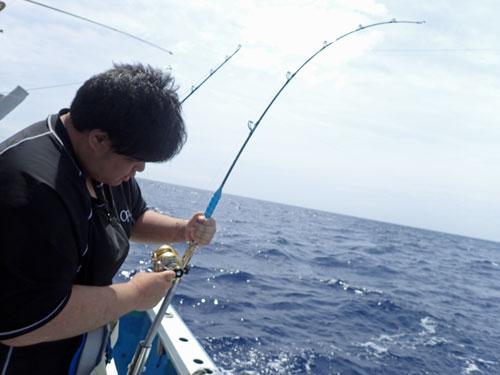 カツオを釣っている黒服の男性