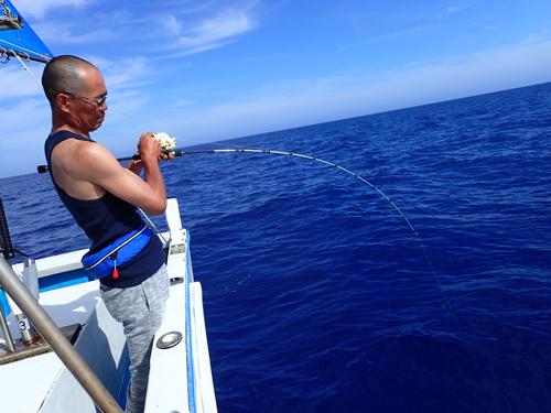 ジギングでカンパチ釣り上げ中の男性