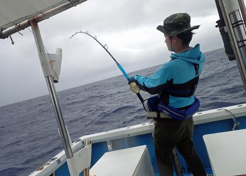 カジキを釣っている男性の左斜め後ろ姿