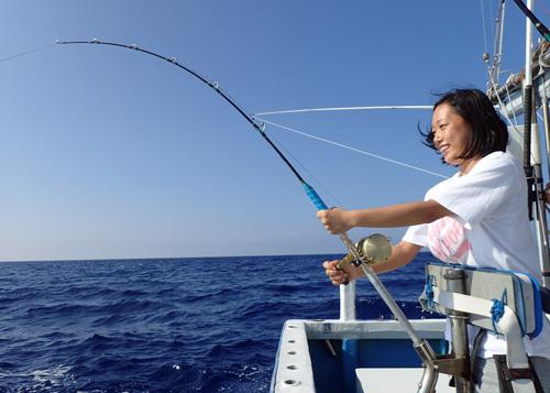 スマを釣っている若い女性