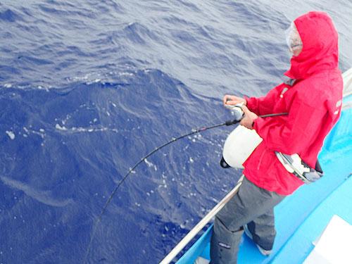 ジギングで魚を釣っている赤いカッパの男性