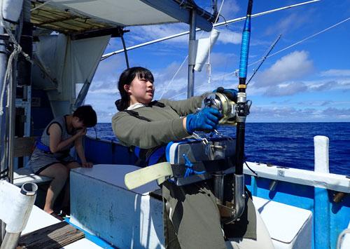カジキを釣っている女子高校生と後ろで船酔いでダウンしている姉