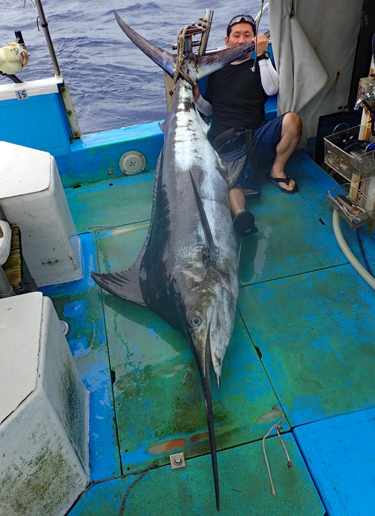 釣り上げた100kgのカジキと釣り上げた男