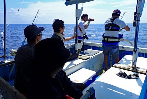 カジキを釣っている男を後ろで見守る仲間たち