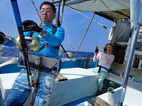 カジキを釣っている男性の後ろで撮影する女性