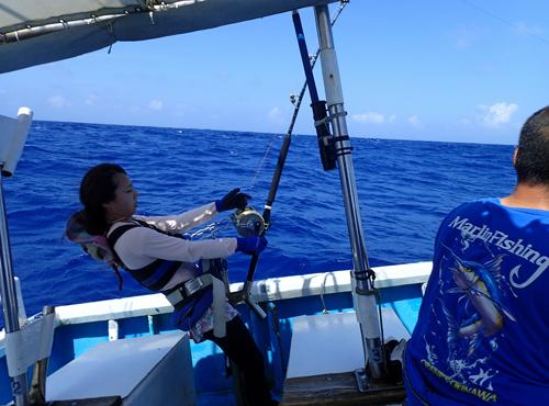 カジキを釣っている女性と鶴巻船長の後ろ姿