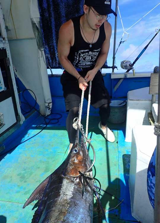 自ら釣り上げたカジキを引き上げる若い男性
